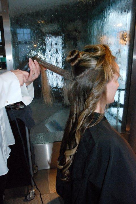 Frisør Beate Søvik Pedersen lager krøller med flatjern for at håret ikke skal bli for tungt i løpet av en hel bryllupsfest.