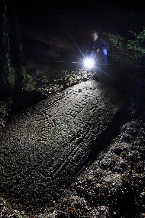 NATTLYSNING: Landskapsarkitekt hos Fylkeskonservatoren, Lars Ole Klavestad, lyser opp helleristninger ved Bakke i Skjeberg.