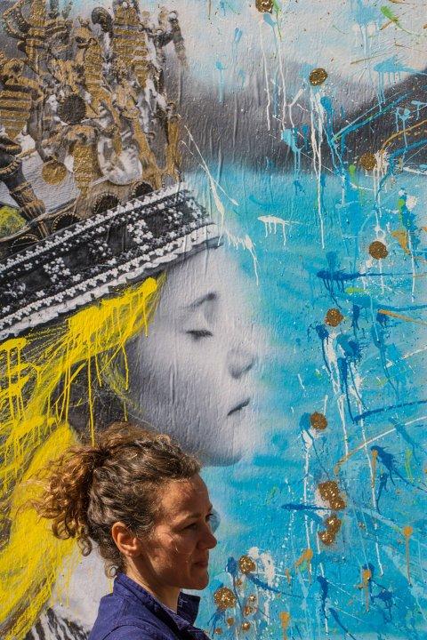Søndag 11. desember blir det miniutstilling og føredrag med gatekunstnarane AFK, Nimi og Sandie Coral Dougnac. Sandie har vakse opp på Husnes, og her står ho med eitt av motiva sine «Fjord Draum». (Pressefoto).
