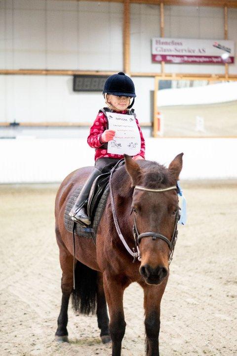 Frida Ingrid Tangen Karlsson på hesten Roxanne fikk utdelt diplom og sløyfe etter sin runde