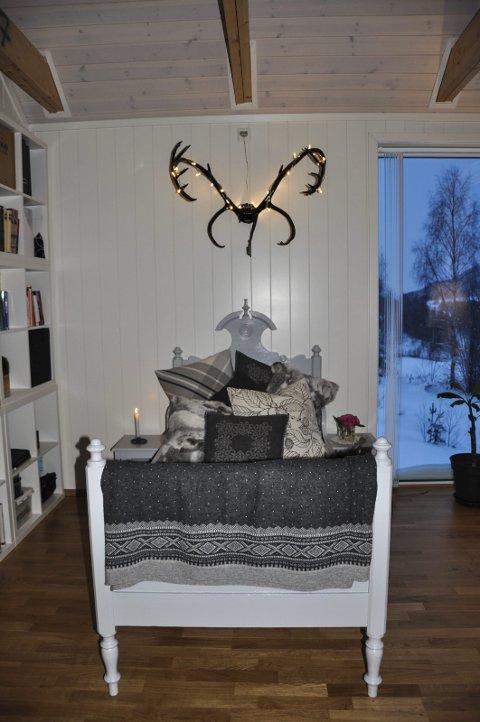 Hornet på veggen: Et reinsdyrhorn malt med svart høyglans, og med påsatte lys, over en oppusset  «day-bed».