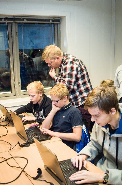 STØTTE: Terje Rove Pettersen (bak) bistår Emil Smith Lillevik (13) med et kodeproblem. Leon Alexander Johannesen (12, midten) og Ludvig Sørlie (17) jobber med sine oppgaver.