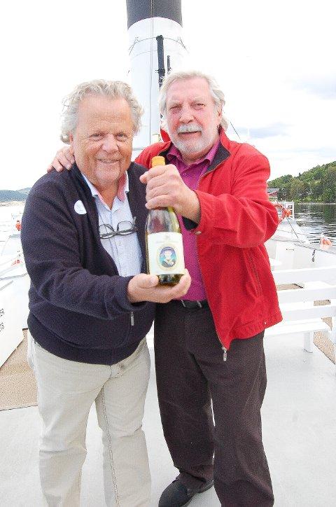 """TO KARER OG EN FLASKE VIN: Billedkunstneren Jan Baker (t.h.) og direkjonsformannen for """"Skibladner"""", Bjørn Blichfeldt, er fornøyd med både etiketten og årets vin."""