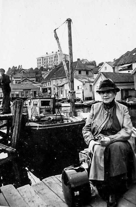 Dette er et fotografi tatt sent på 1930-tallet. En dame har satt seg ned og venter på å få skyss ut i skjærgården. Kanskje hun har kommet med toget? Ved siden av henne står en stor og solid hatteeske. Å gå med hatt var viktig for damer tidligere. I Kragerø var det flere hattebutikker. I bakgrunnen sees Bybrua og Jens Lauersøns plass.