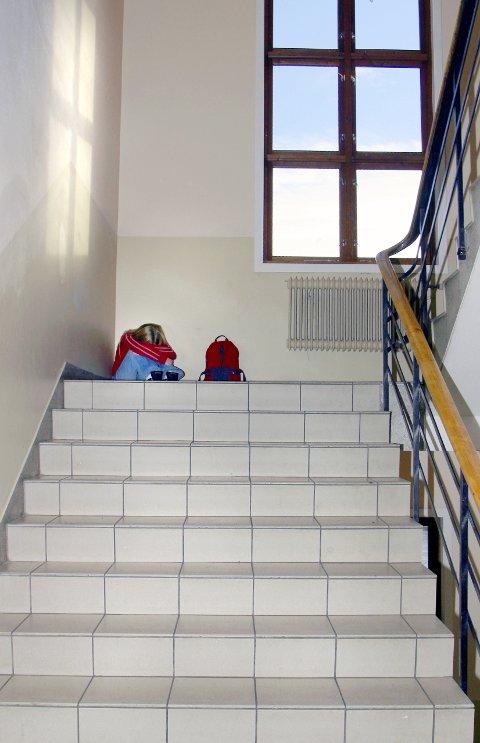 NB! Kun til redaksjonell bruk. En jente sitter sammenkrøpet i en trappeoppgang på skolen. Har blitt ertet, mobbet, trakassert, frosset ut. Venneløs. Trapp. Elever. Elev. Trist. Alene. Ingen venner. Uvenner. Føler seg utenfor. Lei seg. Kranglet. Forlatt. Mishandlet. Skole. Barndom. FOTO: SCANPIX  - - MODEL RELEASED - MODELLKLARERT - -