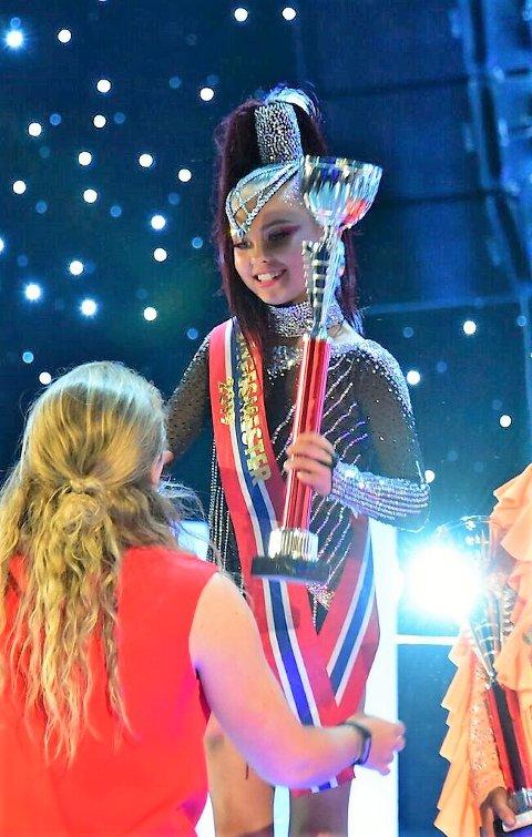 En stolt og glad Kaja Rosseland mottar NM-trofeet for seier i freestyle showdans på 11-årsdagen sin. Foto: Privat