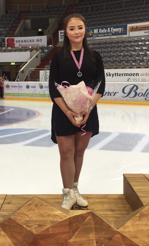 Malin Normann (18) fra Sarpsborg Skøyteklubb tok sølv i NM i kunstløp i Hamar i helgen. Her står hun på pallen etter å ha mottatt medaljen. (Foto: Anna Jurkiewicz)