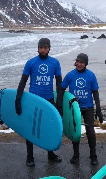 Surfeinstruktør ved Unstad Arctic Surf, Lorentz Bloch Haugland sammen med María Victoria Irigoyen (78) på Brunstranda i Flakstad.