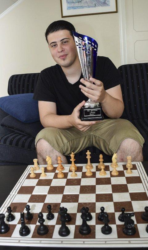 VANT I NM: Ward Al-Tarbosh kom til Norge som syrisk flyktning, og er samtidig en talentfull sjakkspiller. Nylig vant han klasse 1 i NM, og fikk den store pokalen han viser frem.