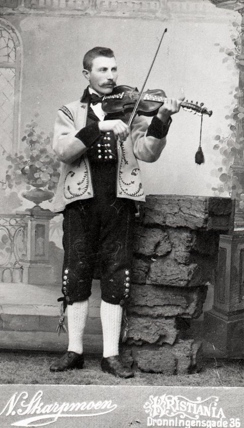 I finstasen: Ola G. Okshovd staselig kledd i bunad hos fotografen i Kristiania, trolig rundt 1900.