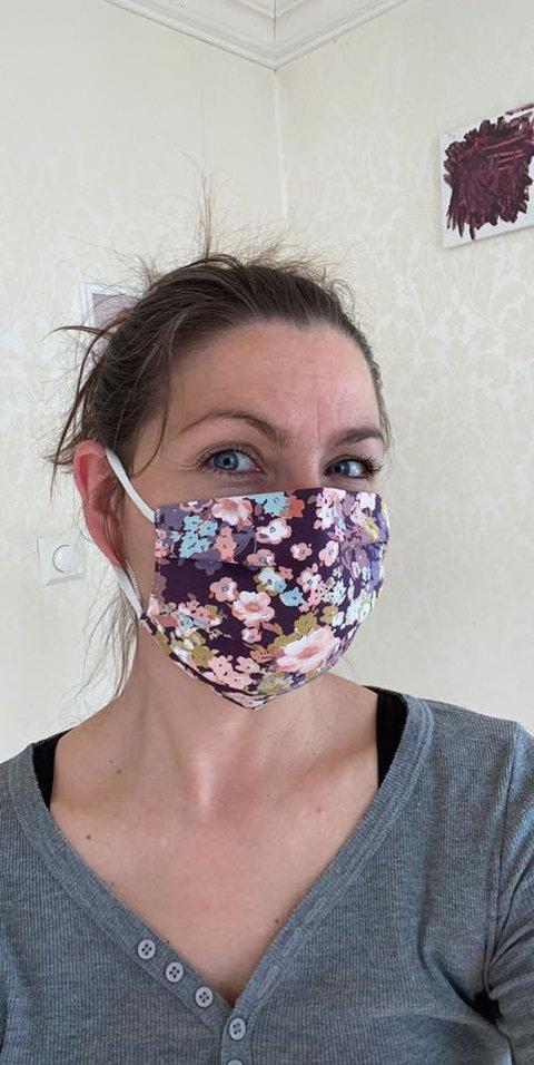 Anne Lise Eriksen med en blomstrete og fargeglad utgave av munnbindene hun har begynt å sy.