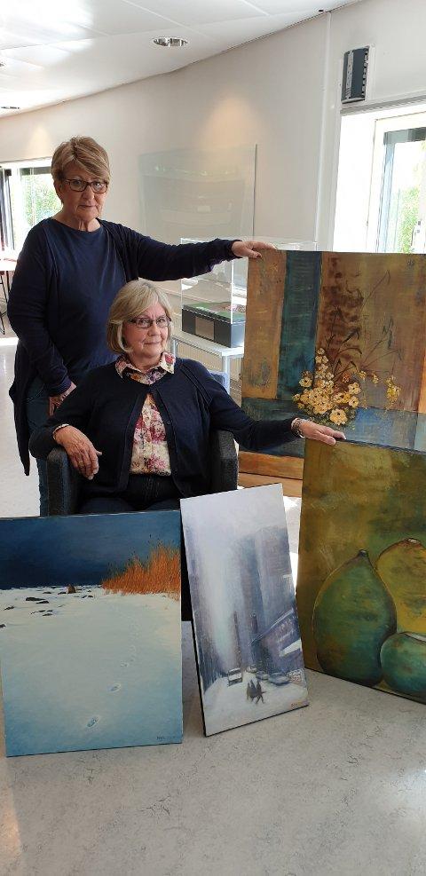 Berit Heggen og Liv Aamot med bilder til å dekorere Jessheim bibliotek.