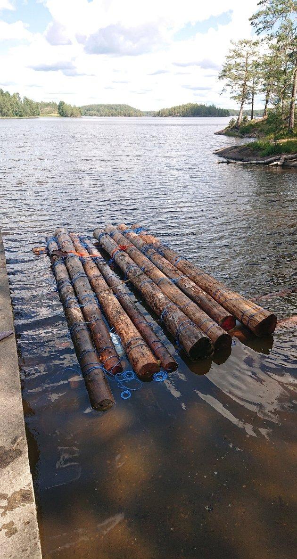 Første lag av flåta, tykke tømmerstokker lagt på langs med tverrleggere under. Alt er festet med vinkelsurringer, inkludert pontonger.