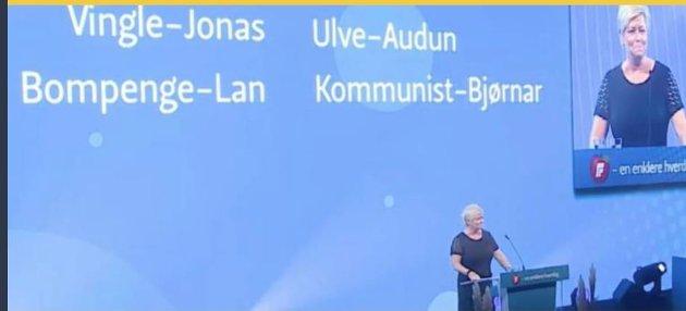 TOK EN «DONALD»: Siv Jensen på talerstolen. Hun deler ut karakteristikker til sine politiske motstandere – og de dukker opp på skjermen bak henne.   Etterpå kokte det i sosiale medier.