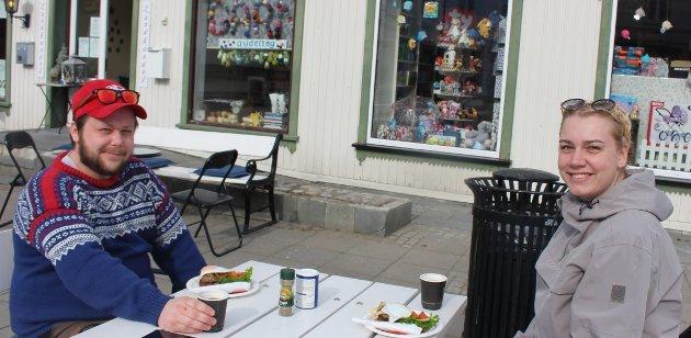 Charlotte Holtsdalen og Terje Vigerust har bestilt og fått servert karbonadesmørbrød med spelegg hos Langesund Landhandel. Lunsjen blir spist ute på torget. – Dette er kjempegodt, sier de.