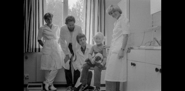 1980: Legesenter åpnet i Ås. Liten jente som pasient, med leger og sykesøstre.