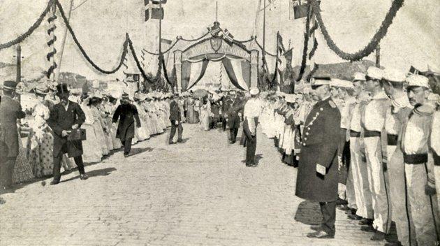 KRONINGSREISEN: Dette gamle bildet ble tatt i forbindelse med kroningsreisen 1906. Kong Haakon og Dronning Maud brukte kongeskipet «Heimdal» på deler av ferden, og på vei til Trondheim avla de Kristiansund et besøk.  Den forbindelse ble det laget en flott portal på Piren, hvor kongen og dronningen gikk i land. Hele byen var på bena for å møte kongeparet. Mannen i sjakett og flosshatt til venstre på bildet er fotograf Johan K. Engvig, som startet fotofirmaet Engvig.  Han drev også kino og representerte Venstre i formannskapet og bystyret. Kroningen i Nidarosdomen skjedde 22. juni 1906, så bildet er tatt noen dager før. Fotografen er ukjent. Postkortet eies av Sissel Engvig.