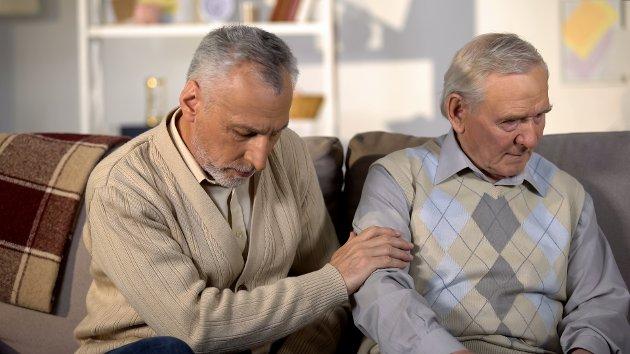 Elderly male comforting senior friend holding hand, loss depression, support