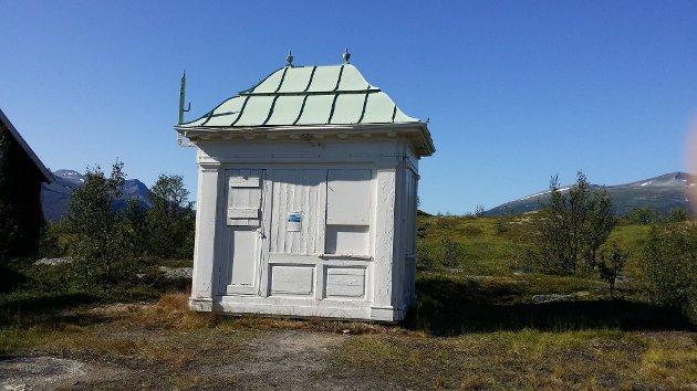 Denne forfalne kiosken på Hella, ca. 100 år gammel,  ble i 1962 reddet fra riving, og flyttet ut til Hella. Den er i likhet med kiosken i hagen til Jos Kögeler og Barbara Vögele i Muségata (Nilssens kiosk) tegnet av arkitekt Peter Arnet Amundsen fra Sogn. Amundsen (1872-1958) begynte som stadskonduktør i Tromsø i 1914 og hadde denne stillingen fram til 1944. Som Statskonduktør skulle han være byens arkitekt, reguleringssjef, og bygningssjef. Han kunne også ta på seg private bidrag. Av hans arbeider i Tromsø kan nevnes Verdensteatret, Det geofysiske institutt, Kongsbakken videregående skole og altså flere av byens små kiosker.