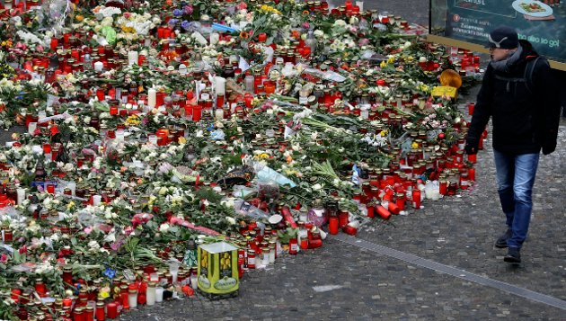 A man walks past flowers close to the Christmas Market at the Breitscheid square in Berlin, Germany, Wednesday, Jan. 4, 2017. A truck ran into a crowded Christmas market and killed several people on Dez. 19, 2016. The Market will be dismantled this week. (AP Photo/Michael Sohn)