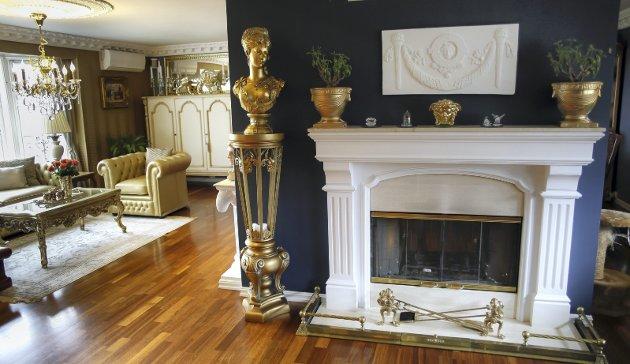 Søyler, rosetter, gipslister med dekor og møbler og detaljer i gull.  Bak veggen med peis er spisestua, også denne har peis.