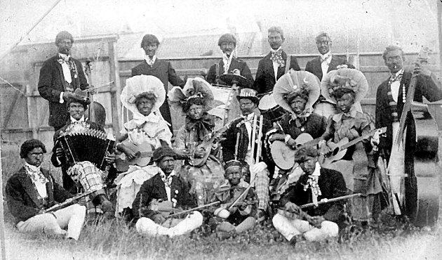 Vi har ingen opplysninger om hvilke musikere som skjuler seg bak masker og sminke på dette festlige bildet fra 1920, annet enn at det er et Sarpsborg-ensemble. (Sarpsborg    kommunes fotosamling).
