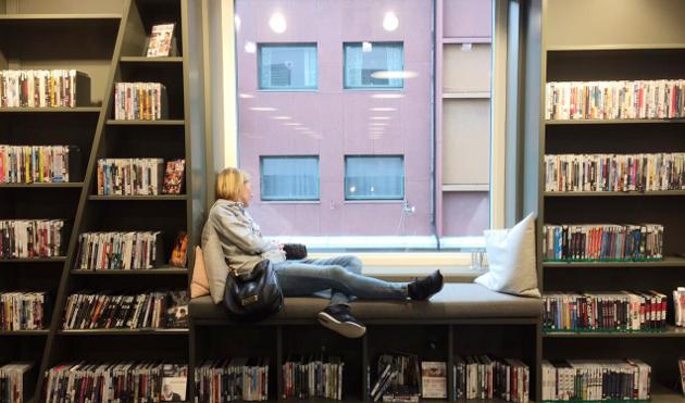 """LES OG FØLG MED: I det store vinduer går det an å følge med på livet i byen. Eller slappe av med en bok. Veggen kalles """"fjellhylla"""", og viser til det bratte Holmestrandsfjellet som ligger bak biblioteket."""