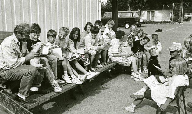 """Før i tida var det vanleg å innimellom ha """"dyredag"""" på skulane. Då kunne elevane ta med seg kjæledyra sine og visa dei fram. Kanskje skjer det rundt om på skulane enno, utan at vi skal seia det heilt sikkert. Dette bildet er i alle fall frå ein slik dyredag på Seglem skule i 1992, der rektor Vidar Haugland viser fram ein herleg grisunge."""