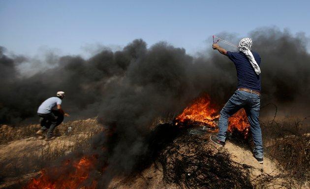 Konflikten fortsetter: Første betingelse for håp om fred er at palestina-araberne aksepterer at Israel har krav på en stat med sikre grenser, skriver innsenderen. Her ser vi palestinere som kaster stein mot grensen til Israel på Gazastripen 8. juni. Foto: NTB scanpix / AP