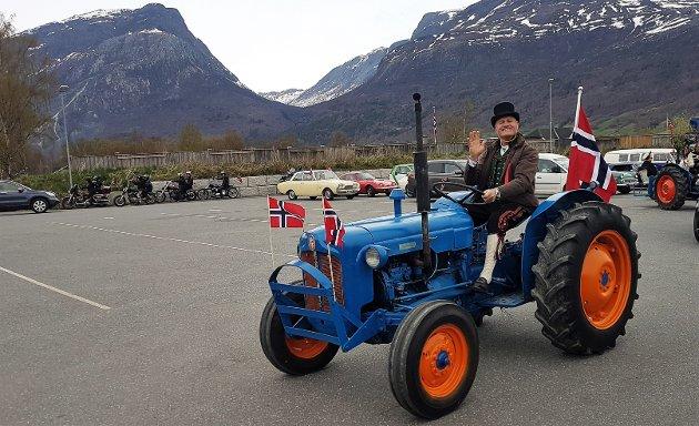 Staselig: Helge Lajord vinker smilende og fornøyd bak rattet på traktoren under bilkortesjen i Vang.