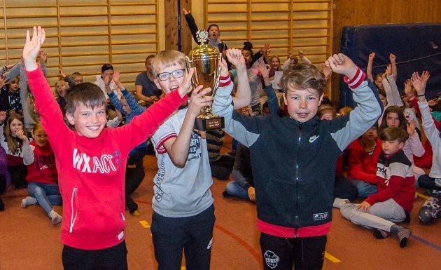 Sykkelgutta Josten Skagemo (4.klasse, t.v.), Eivind Eikemo (6. klasse) og Sivert Ødegård Engen (5. klasse) kan stolt heve pokalen for årets sykkelseier over hodet til stor jubel fra resten av skolens elever. Kroer skole er Follomester i sykkelferdigheter for tredje året på rad i NAF-konkurransen  «Sikker på sykkel».