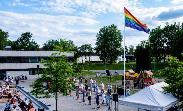 ÅsEnsemblet holder allsang uten grenser i borggården foran Ås rådhus, og kommunens Pride-flagg vaier i vinden.