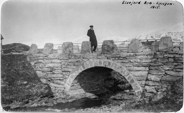 Elvejord Bro. En mann med frakk og sixpencelue går over steinhvelvsbrua med stabbesteinsrekkverk. I bakgrunnen er det snødekte fjell. Mannen er sannsynligvis Nicolai Olaf Saxegaard.