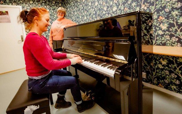 NYE TANGENTER PÅ PLASS: Bibliotekat Helene Fagerhus nyter de første toner fra det nye pianoet, spilt av kulturhusleder Myfanwy Moore.