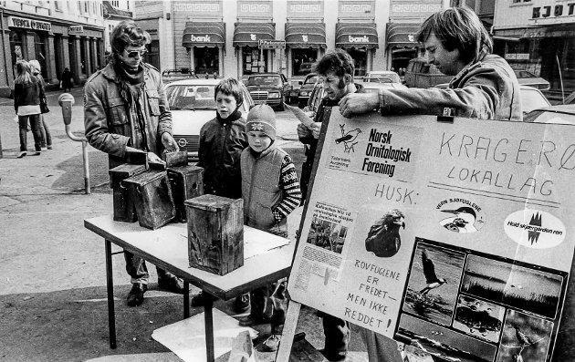 """Norsk Ornitologisk forening hadde stand på Kragerø Torv, hvor de blant annet solgte fuglekasser. Hvem er det på bildet? Mannen til venstre kan minne om en yngre utgava av Steinar Sannes? Mannen som studerer en brosjyre er Øystein Glette. I Bakgrunn ser man et skilt som forteller at meieriet fortsatt hadde utsalg i Torvgata. Like ved ser man kontorene til forsikringsselskapet """"Vesta""""."""