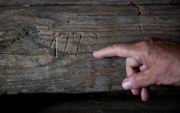 Husmannsplassen Hesthagen i Ringsaker. Else Rønnevig peker på det eldste innrisset hun har funnet i tømmerstokkene på det ene huset.