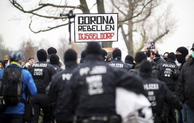 – Det er nesten underlig hvordan radikale venstre og radikale høyre i en rekke land har latt seg forene under parolen om at «korona er en konspirasjon», skriver Jana Midelfart Hoff. Bildet fra en demonstrasjon i Düsseldorf. Foto: Jonas Guettler/AP