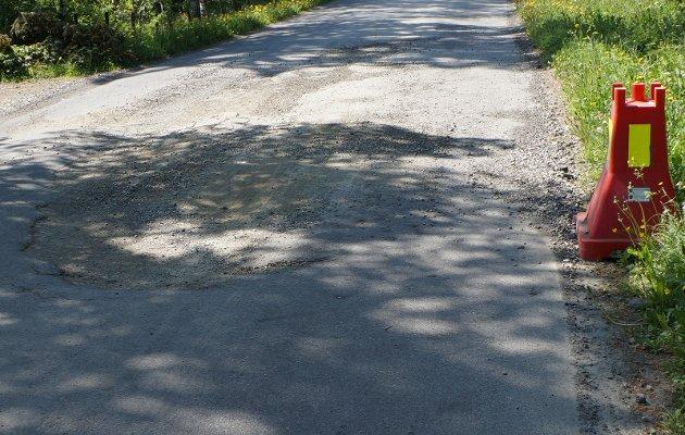 ØDELAGT VEG: I Raastadbakka ved Stubnekrysset har vegen gått i oppløsning og skadene er langt verre enn dette bildet viser. I tillegg har kommunen ikke tatt bryet med å sette opp varselskilt nr. 108.