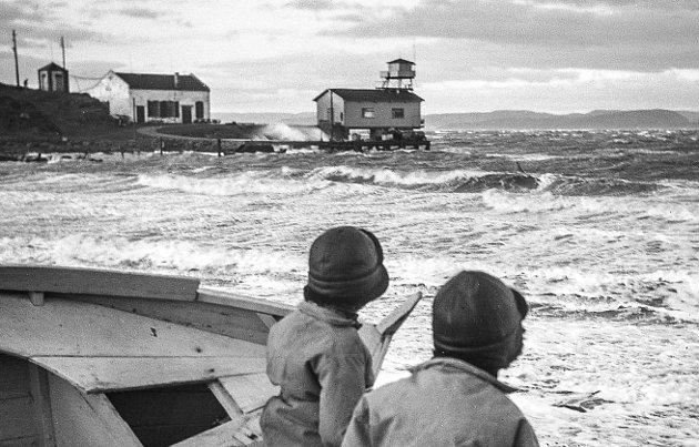 UTE I BLÅSTEN: Bildet viser torpedostasjonen tidlig på 50-tallet. Brødrene Olaf og Tor Schmedling står på Tronvikstranda og følger med på ruskeværet.