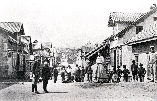 STORGATEN i Stavern på bilder fra før og etter århundreskiftet. Bildet er tatt fra Utsikten like etter bybrannen i 1883. En del av husene har ennå ikke fått kledning utenpå tømmerveggene, og gatetrærne er ikke plantet.