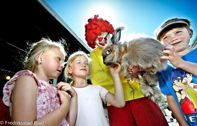 Borgedagene på Selbak Torg: Maja (5), Therese (6) og Thomas (7) hilser på kaninen Labbetuss mens den sitter trygt på armen til klovnen Osmondo. Foto: Kent Inge Olsen, 15.06.2006