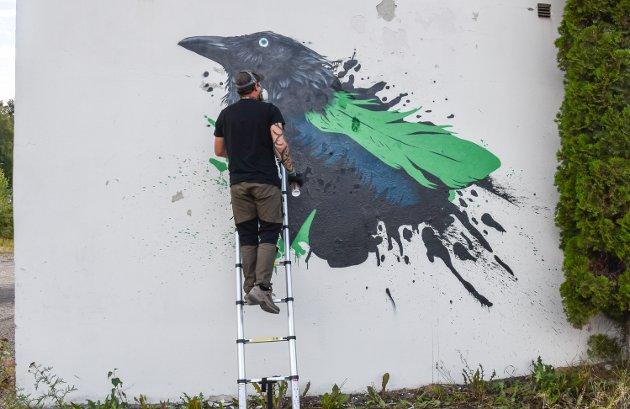 TAKKNEMLIG: Maik Detzner har malt denne ravnen på en hvit vegg på Melby-tomta. Dette tåler vi mer av i Elverum.