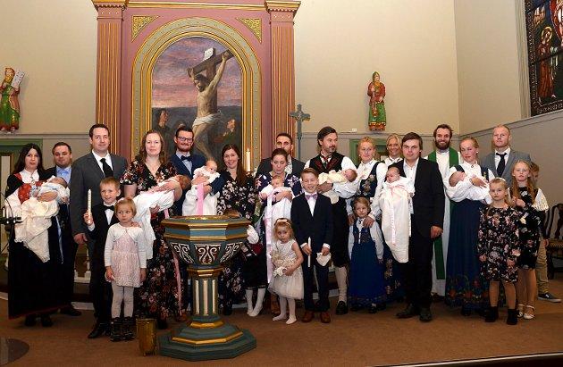 DÅPSREKORD: Syv av de rekordartede åtte dåpsbarna med sine nærmeste, samt prest Preben Axel Hodt, samlet foran alteret i Askim kirke etter dåpsgudstjenesten.