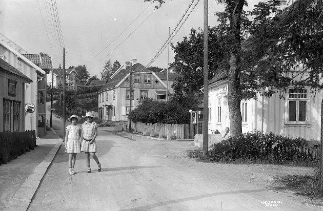 To piker på Kongeveien i Hølen. Selviggården i bakgrunnen og Apotekergården til høyre.