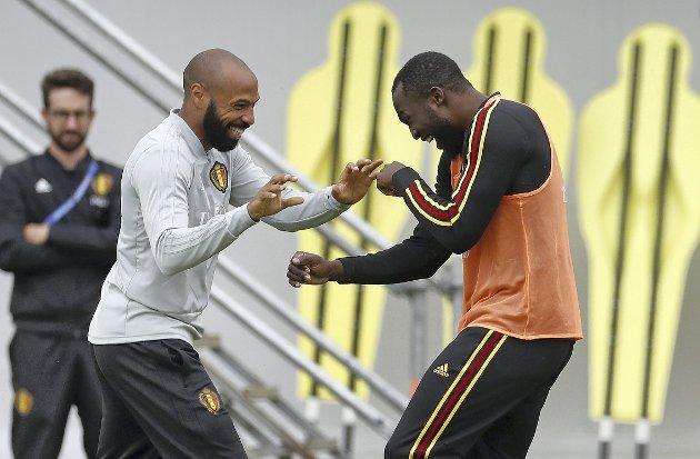 Humøret er på topp hos franskmannen Thierry Henry (t.v.) og Romelu Lukaku før VM-semifinalen mot Frankrike i tirsdag. Henry er med i det belgiske trenerapparatet. (Foto: NTB scanpix)
