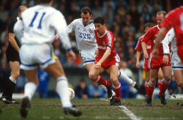 Sesongen 1990/91:  Ian Rush løper forbi Gary McAllister (Leeds). Den regjerende ligamesteren Liverpool begynte sesongen med Kenny Dalglish som manager, men han trakk seg den 22. februar 1991. Bakgrunnen var presset han følte etter Hillsborough, hvor 96 Liverpool-fans døde. I etterkant har han selv sagt at han hadde en tro på at Liverpool kanskje ville vente til sommeren med å utnevne ny manager, men Liverpool ga jobben til Graeme Souness fem kamper før slutt (Ronnie Moran tok over i mellomtiden).  Liverpool endte på en 2. plass i serien, 7 poeng bak seriemesterne Arsenal. 13 poeng foran Gary McAllisters nyopprykkede Leeds på en fjerdeplass.  I bakgrunnen på bildet (til venstre) ser du David Speedie, som ble kjøpt fra Coventry for å erstatte Peter Beardsley (delvis skjult bak) etter at hans form begynte å dale. Begge ble solgt etter sesongen var over. Steve McManaman spilte sine første minutter for Liverpool denne sesongen.   Liverpool vant denne kampen bildet er fra 5-4 på Elland Road. John Barnes (2), David Speedie, Roy Houghton og Jan Mølby laget målene for Liverpool. Lee Chapman laget hat-trick for Leeds.   (Foto: Mark Leech/Offside/Getty Images)