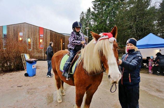 Silja Hallan Remme (7) fikk seg en ridetur i regnet med assistanse av Anne Kari Ryen fra Glemmen gård.