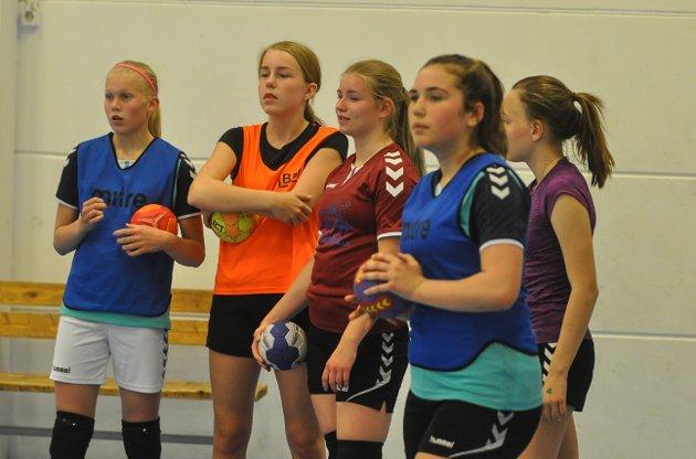 Jentene lytter mens treneren forklarer.