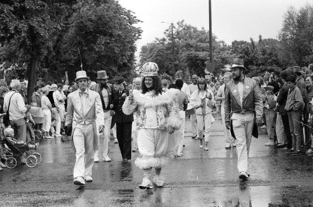 Fra karnevalet i Gamlebyen i Fredrikstad i juni 1984: Kai Jarild (t.v.), Olav Kjeldsen (bak t.v.) og Tore Skofterud i arrangementskomiteen i spissen av opptoget sammen med karnevalskongen i Rio, Ray Momo. Foto: Harald Nielsen, FB 19.06.1984