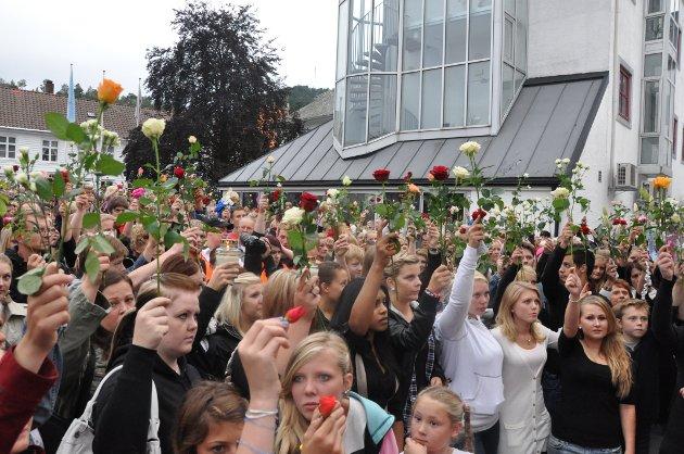 HEDRET OFRENE: Tusenvis av mennesker løftet rosene for å minnes terrorofrene, da mer enn 3000 flekkefjæringer gikk i rosetog gjennom Flekkefjords gater.